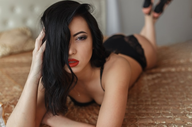 그녀의 속옷에 침대에 누워 아름 다운 젊은 여자의 초상화.