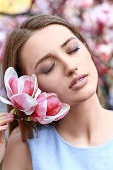 屋外で咲くモクレンの木の近くの美しい若い女性の肖像画