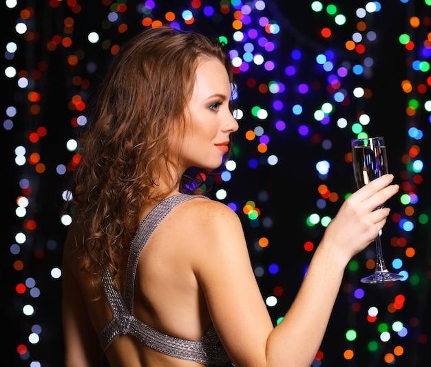 Портрет красивой молодой женщины на фоне ярких огней