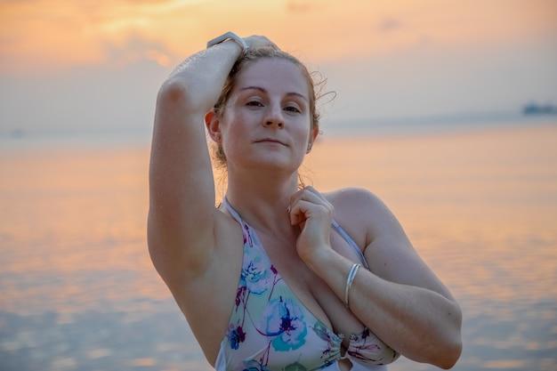 Портрет красивой молодой женщины на фоне заката у моря