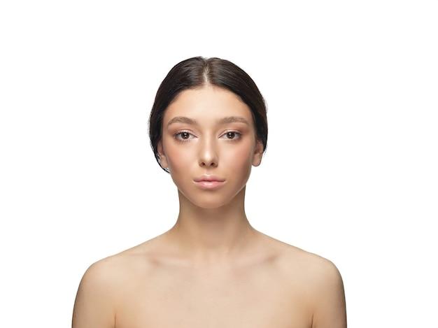 白いスタジオで美しい若い女性の肖像画