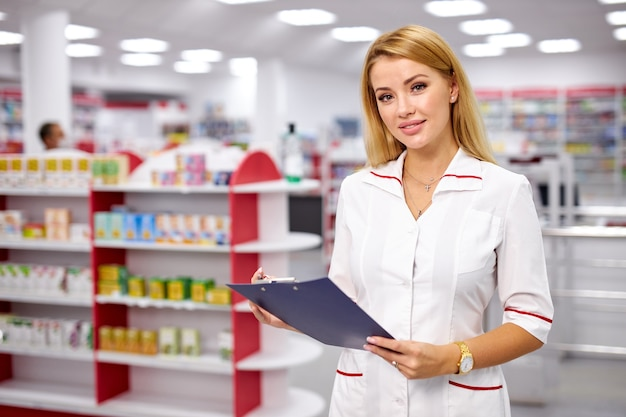 현대 약국에서 제복을 입은 아름 다운 젊은 여자 약사의 초상화
