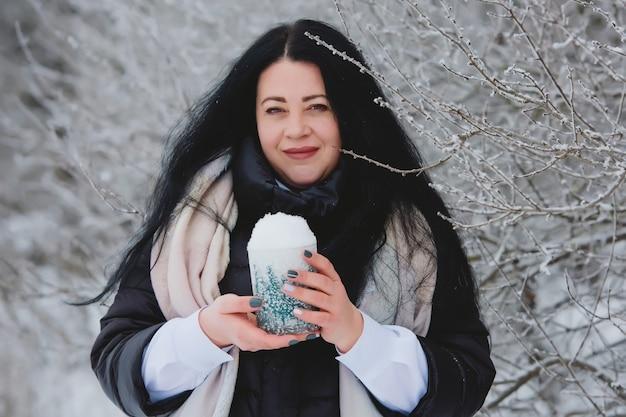 雪で遊ぶ美しい若い女性の肖像画。