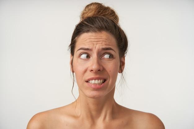 Портрет красивой молодой женщины, позирующей на белом без макияжа, смотрящей в сторону с сомневающимся лицом, сжимающей брови и показывая зубы