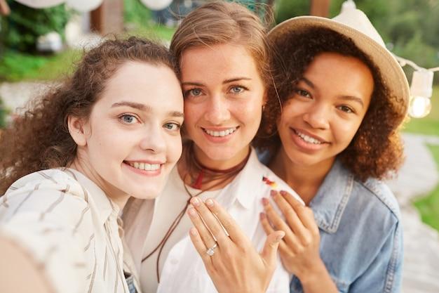 屋外パーティー中に友人と自分撮りを取っている婚約指輪を示す美しい若い女性の肖像画