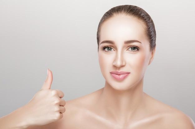 Портрет красивой молодой женщины показывает палец вверх жест на сером фоне
