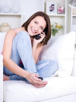 ソファに座って、電話で話し、ペディキュアを作る美しい若い女性の肖像画