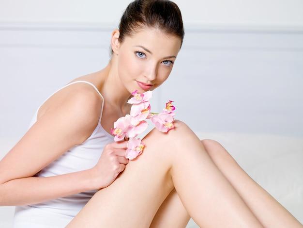 Портрет красивой молодой женщины, сидящей с цветком - в помещении