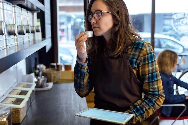 オーガニックショップで重量で販売されている茶葉の匂いを嗅ぐ美しい若い女性の肖像画。