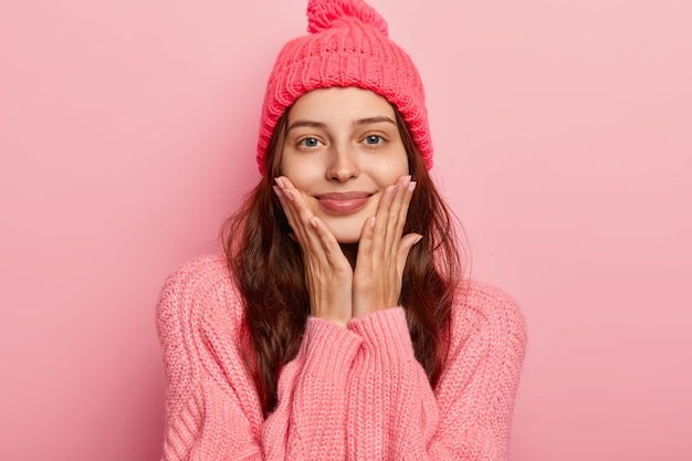 아름 다운 젊은 여자의 초상화는 즐겁게 미소를 지으며, 두 손바닥을 뺨에 유지하고, 기꺼이 카메라를 바라보고, 편안한 표정을 가지고 있으며, 니트 겨울 모자와 스웨터를 입고, 분홍색 스튜디오 벽 위에 실내 모델을 착용합니다.