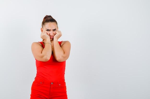 Портрет красивой молодой женщины, дующейся щеками, опираясь на руки в красной майке, брюках и обиженной, вид спереди