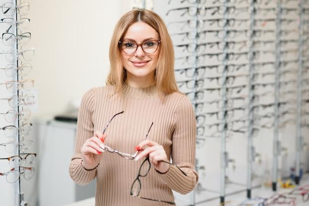 Портрет красивой молодой женщины пробует новые очки в магазине оптики