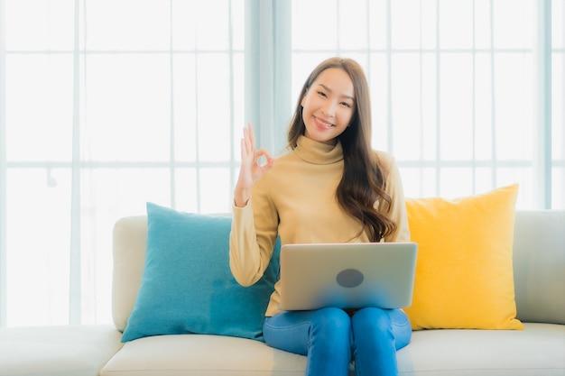 リビングルームのソファーにラップトップを使用して美しい若い女性の肖像画
