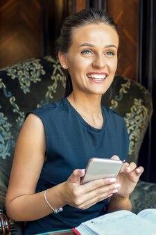 Портрет красивой молодой женщины с помощью мобильного телефона дома.