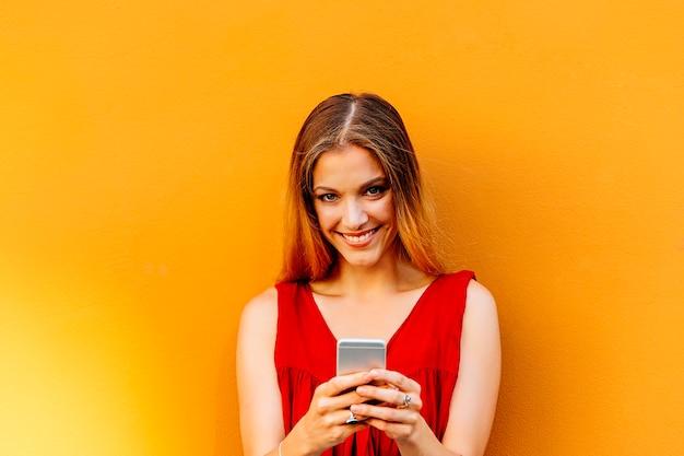 通りで携帯電話を使用して美しい若い女性の肖像画。モバイルコンセプト。