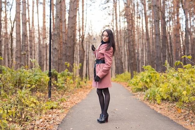 秋の屋外を歩く美しい若い女性の肖像画。
