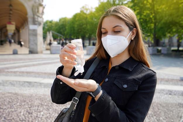 도시 거리에서 그녀의 손을 소독 알코올 젤을 사용하여 kn95 ffp2 보호 마스크를 착용하는 아름 다운 젊은 여자의 초상화.