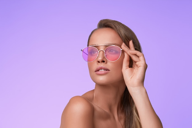 赤いサングラスをかけている美しい若い女性の肖像画。官能的なファッションモデル