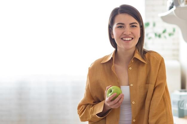 台所で家に立っているリンゴと美しい若い女性の肖像画。健康的なライフスタイルのコンセプト