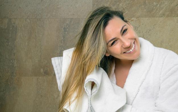 シャワーの後にタオルで彼女の濡れた髪を拭くバスローブと美しい若い女性の肖像画。健康と美容のコンセプト。