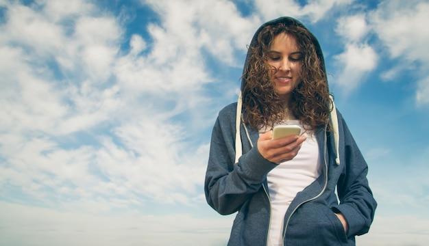 흐린 푸른 하늘 배경에서 스마트폰을 바라보는 파란색 후드티와 운동복을 입은 아름다운 젊은 여성의 초상화