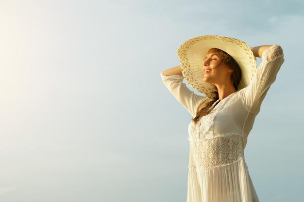 ビーチにつばの広い帽子を持つ美しい若い女性の肖像画