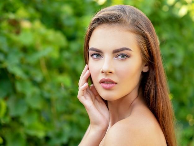 깨끗 한 얼굴을 가진 아름 다운 젊은 여자의 초상화입니다. 깨끗하고 신선한 피부를 가진 젊은 성인 여자의 아름다운 얼굴-자연. 야외에서 젊은 아름 다운 섹시 한 여자의 얼굴입니다. 젊은 여자의 아름다움 얼굴입니다.