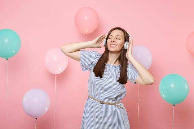 Портрет красивой молодой женщины с закрытыми глазами с наушниками в голубом платье, слушая музыку на пастельно-розовом фоне с красочными воздушными шарами. день рождения праздник у людей искренние эмоции.
