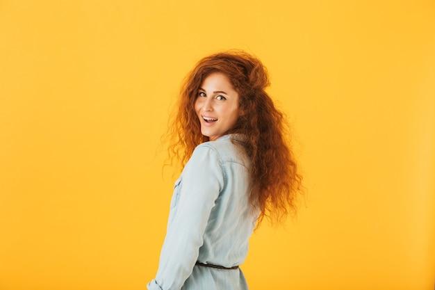 黄色の背景で隔離のカメラに微笑んで巻き毛を持つ美しい若い女性の肖像画