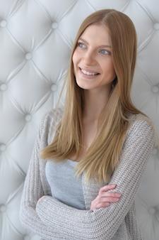 深い青色の目と交差した腕を持つ美しい若い女性の肖像画