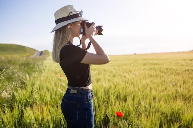 Портрет красивой молодой женщины с цифровой камерой, фотографирующей в поле.