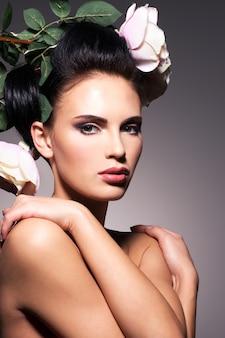 머리에 꽃을 가진 아름 다운 젊은 여자의 초상화 포즈