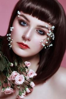 彼女の顔に花を持つ美しい若い女性の肖像画。韓国風メイク、人形の美しさ