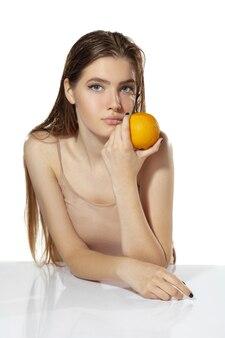 Портрет красивой молодой женщины со свежим апельсином возле лица на белом фоне. концепция косметики, макияжа, натуральных и экологических процедур, ухода за кожей. блестящая и здоровая кожа, мода, здравоохранение.
