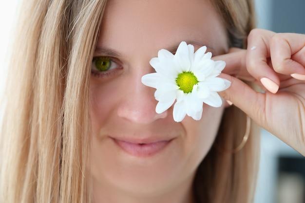 Портрет красивой молодой женщины с зелеными глазами закрывает один глаз цветком