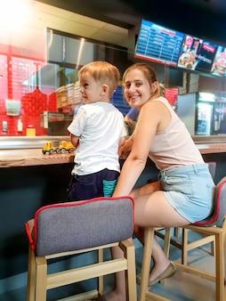 어린 아들과 함께 카페의 긴 카운터 데스크 뒤에 앉아 음식을 기다리는 아름다운 젊은 여성의 초상화