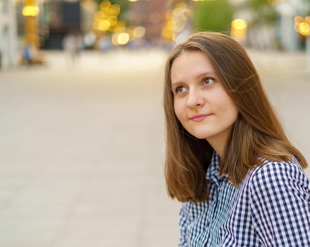Портрет красивой молодой женщины с длинными светлыми волосами, глядя на город