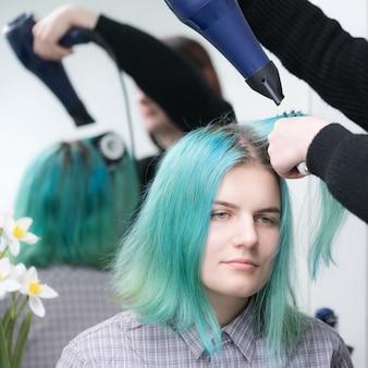 미용실에서 머리를 말리고 스타일링하는 동안 긴 녹색 머리를 가진 아름다운 젊은 여성의 초상화...
