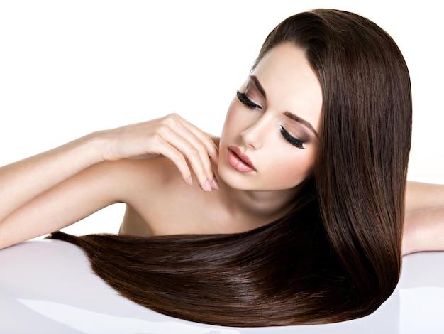 Портрет красивой молодой женщины с длинными прямыми каштановыми волосами, изолированными на белом