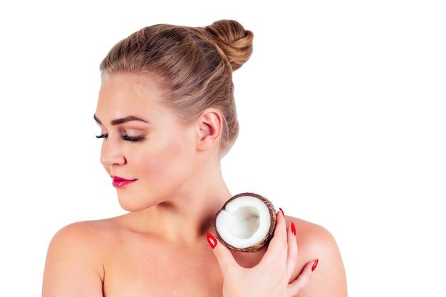 스튜디오 흰색 배경에 코코넛을 들고 있는 완벽한 피부를 가진 아름다운 젊은 여성의 초상화, 피부와 헤어 테마를 위한 스파, 화장품 유기농 오일