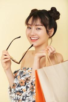サングラスを脱いでカメラを見て買い物袋を持つ美しい若い女性の肖像画