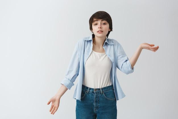 彼女が何も理解していないことを示す手で身振りで示す短い髪の美しい若い女性の肖像画。ボディランゲージ。