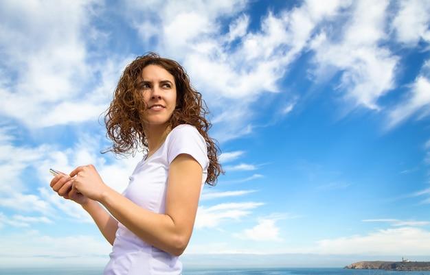 흐린 푸른 하늘 배경 위에 스마트폰을 바라보는 운동복을 입은 아름다운 젊은 여성의 초상화