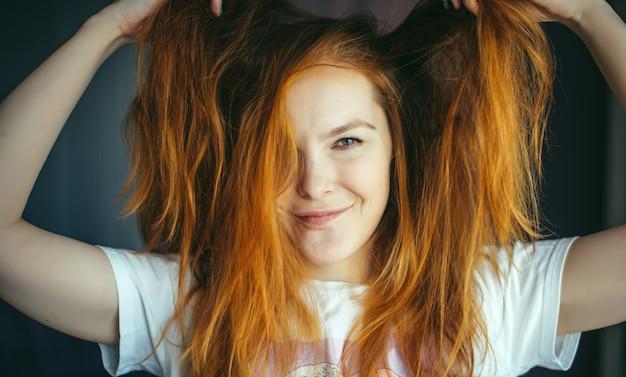 Портрет красивой молодой женщины с густыми растрепанными рыжими волосами, крупным планом. зеленоглазая красотка трогает волосы, глядя в камеру и улыбаясь. реклама ухода, окрашивания волос.