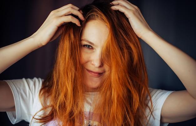 太く、乱れた赤い髪、クローズアップの美しい若い女性の肖像画。カメラを見て笑っている間、緑色の目の美しさは彼女の髪に触れます。ケアの宣伝、ヘアカラー。