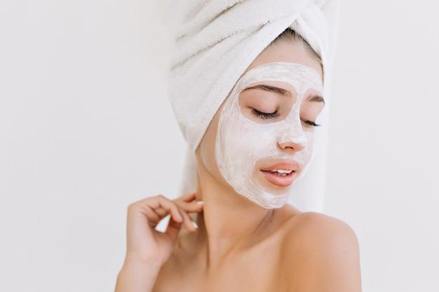 걸릴 목욕 후 수건으로 아름 다운 젊은 여자의 초상화는 그녀의 얼굴에 화장품 마스크를 확인합니다.