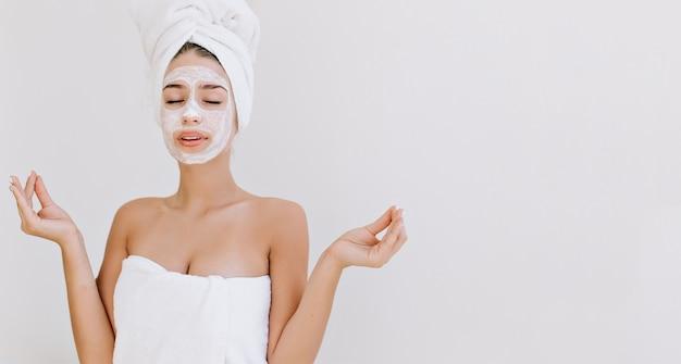 Портрет красивой молодой женщины с полотенцами после принятия ванны делает косметическую маску на лице.