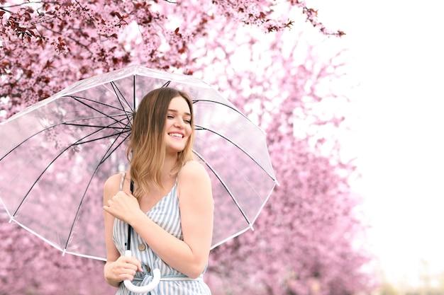 春の日に公園で傘を持つ美しい若い女性の肖像画