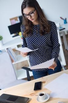 彼女のオフィスで働く美しい若い女性の肖像画。