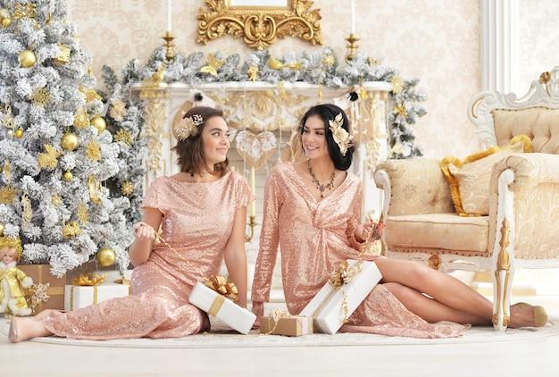 Портрет красивой молодой женщины, сидящей на полу в комнате, украшенной к празднику рождества